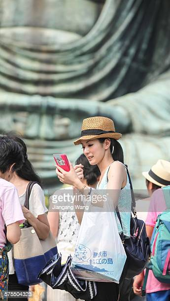 Young woman using cellphone in front of the Great Buddha of Kamakura