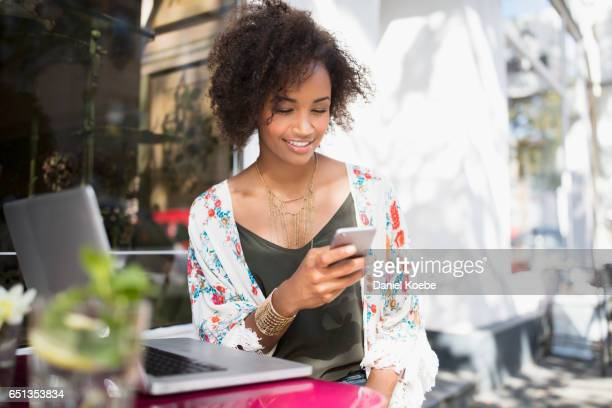 young woman using cellphone outside café