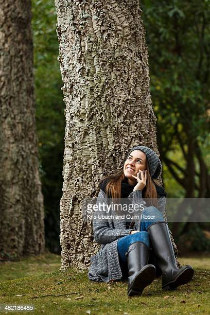 Young woman using cellular phone in forest