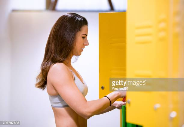 young woman using changing clothes in locker room - ロッカールーム ストックフォトと画像