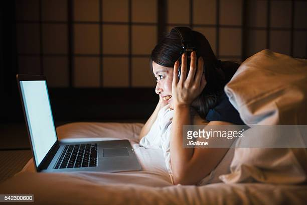 Young woman using computer in bed