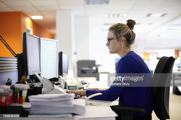 young woman using computer in office - microsoft stock pictures, royalty-free photos & images