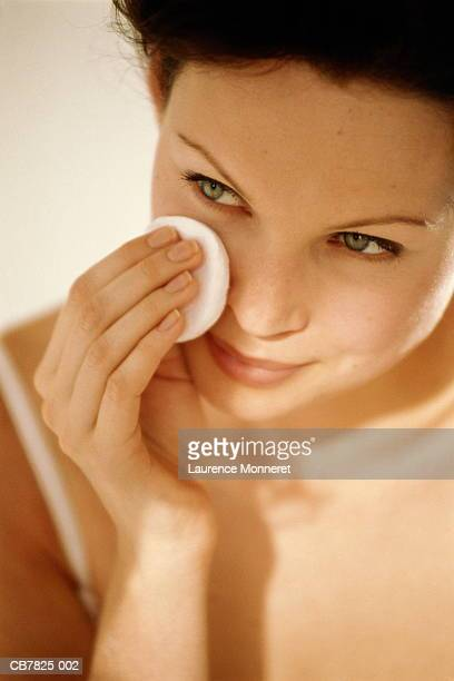 Young woman using cotton wool to wipe face, close-up