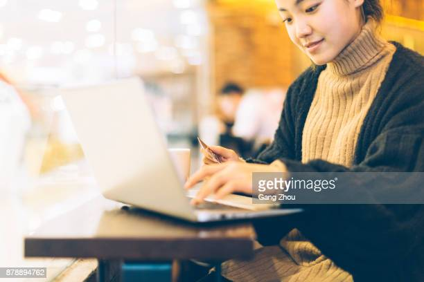 young woman using credit card and laptop in cafe