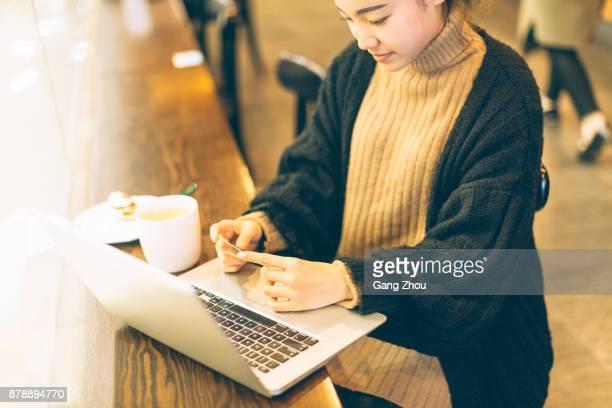 junge Frau mit Kreditkarte und Laptop im café