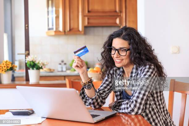 Young woman using credit card at home