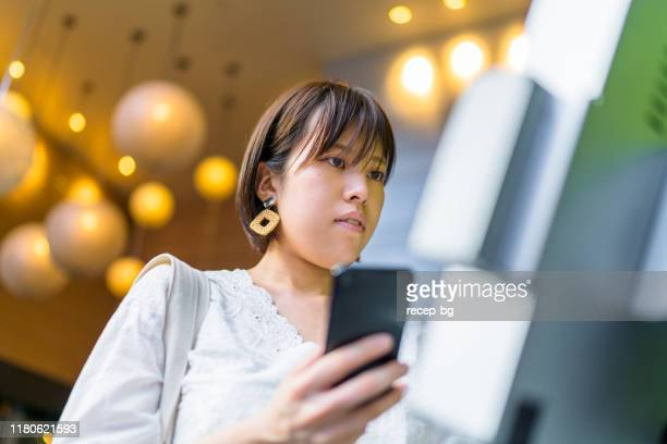 young woman using digital device at counter - kiosk stock pictures, royalty-free photos & images