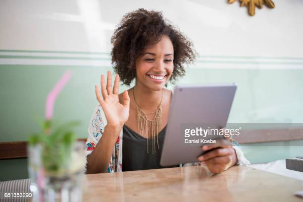 young woman using digital tablet at café - waving gesture stock photos and pictures