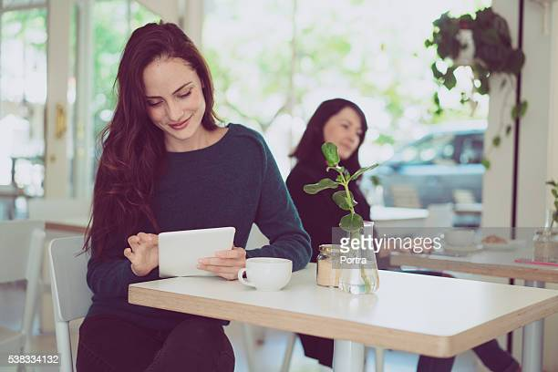 Young woman using digital tablet at cafe table