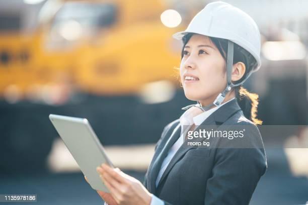 建設現場でデジタルタブレットを使用している若い女性 - 建設現場 ストックフォトと画像