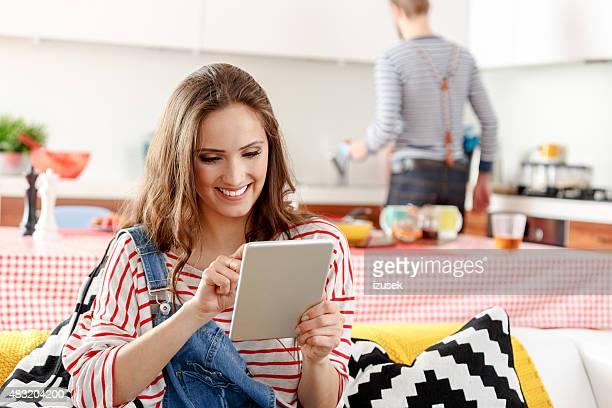 Jeune femme à l'aide de tablette numérique à la maison