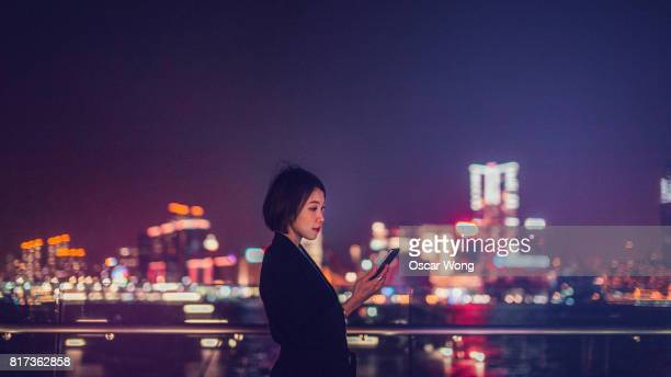 Young woman using digital tablet by the harbor at night