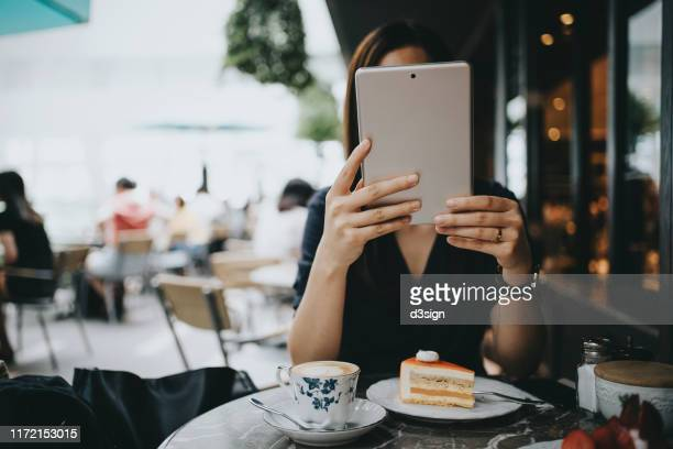 young woman using digital tablet in an outdoor cafe - obscured face stock pictures, royalty-free photos & images