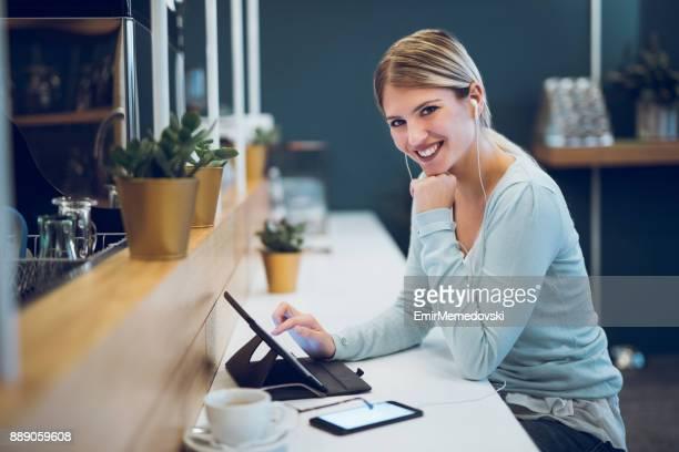 若い女性のコーヒーバーでデジタル タブレットを使用します。