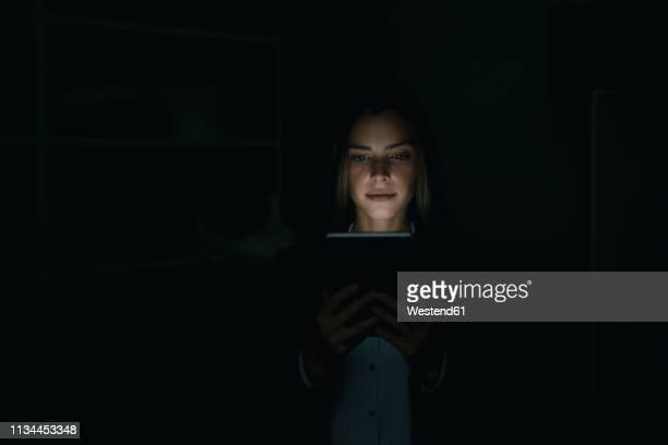 young woman using digital tablet in he dark - junge frau rätsel stock-fotos und bilder