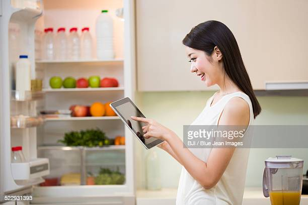 young woman using digital tablet in kitchen - sleeveless stock pictures, royalty-free photos & images