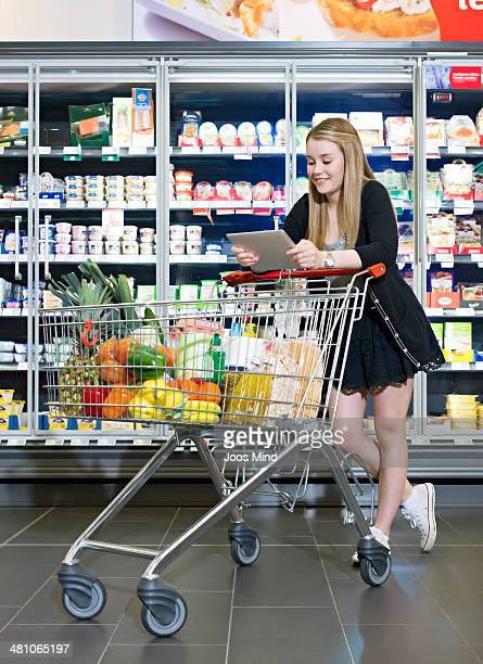 young woman using digital tablet in supermarket