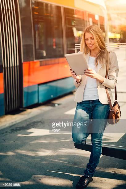 Junge Frau mit Tablet PC auf dem Busbahnhof.