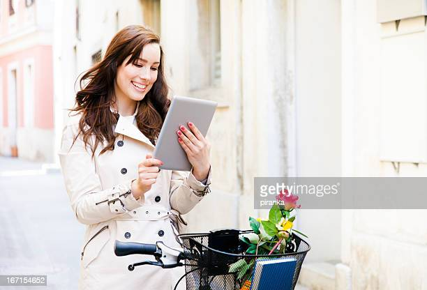 Young woman using digital tablet on city street