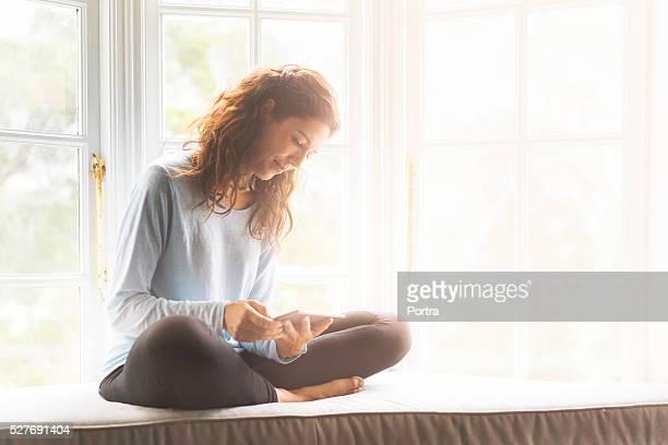 Junge Frau benutzt Digitaltablett auf Fensterbank