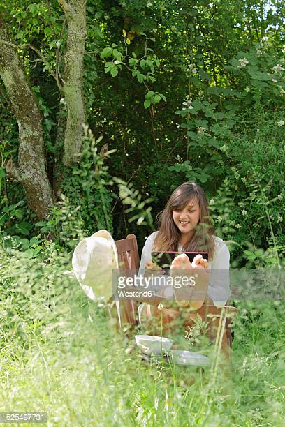 young woman using digital tablet on wooden bench in a garden - woman soles stock photos and pictures