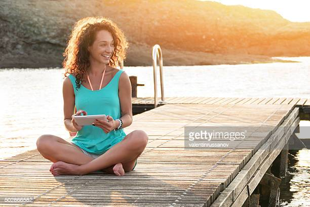 Young woman using digital tablet sitting on the pier