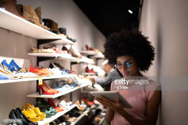young woman using digital tablet to check invetory at a shoe store - shoe store stock pictures, royalty-free photos & images