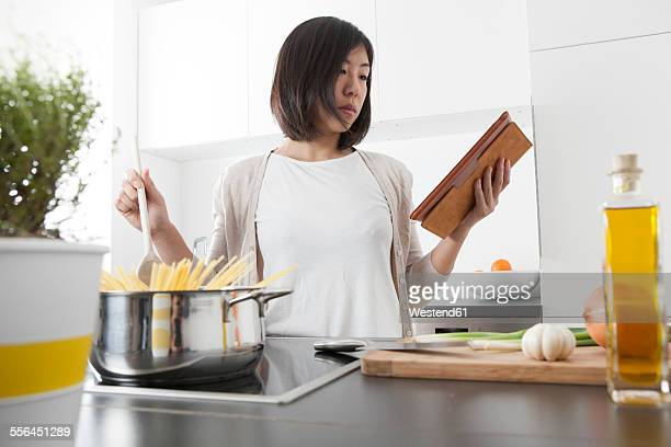 Young woman using digital tablet while cooking spaghetti