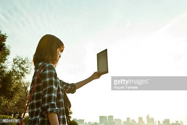 Young woman using digital tablet with skyscraper