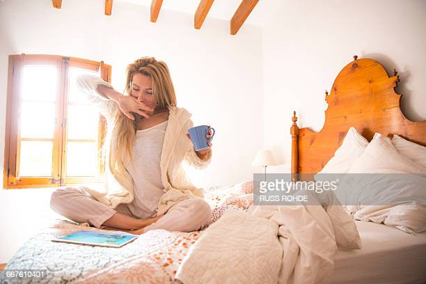 young woman using digital tablet yawning in bed in morning - nightwear stock pictures, royalty-free photos & images