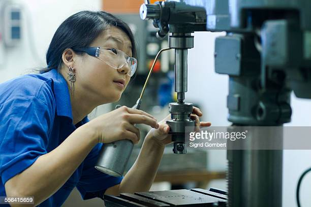 young woman using drill in industrial workshop - sigrid gombert foto e immagini stock