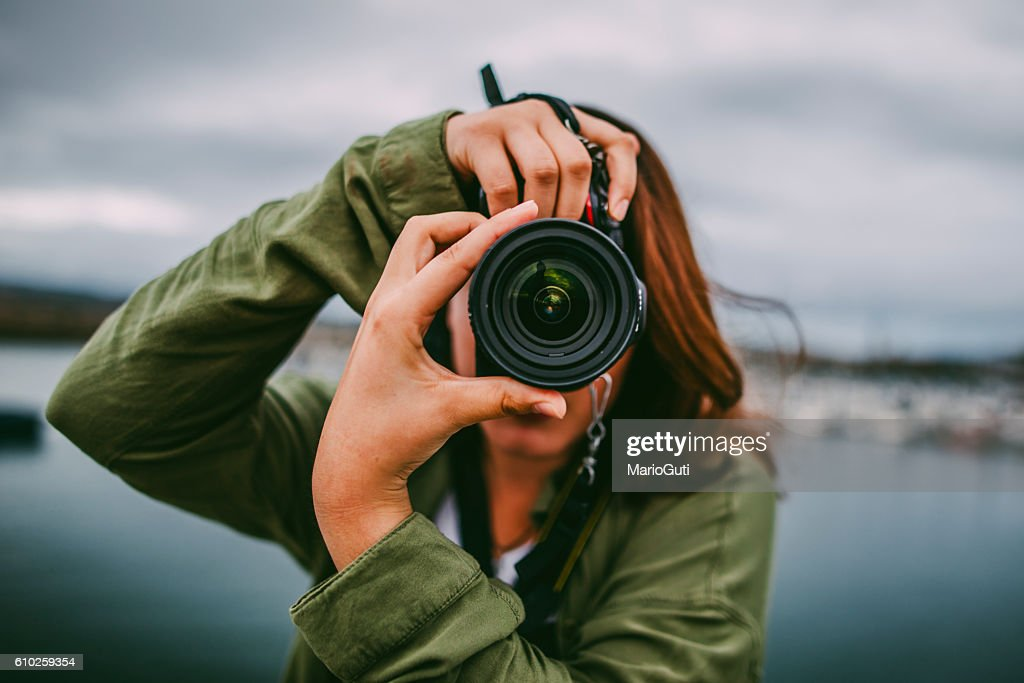Young woman using DSLR camera : Stock Photo
