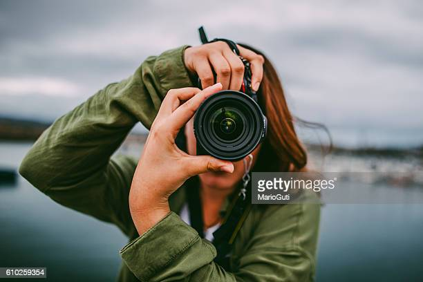 young woman using dslr camera - foto stockfoto's en -beelden