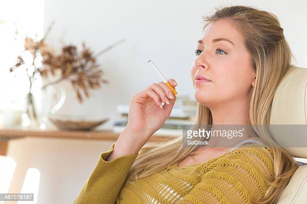 young woman using electric cigarette - beautiful women smoking cigarettes stock photos and pictures