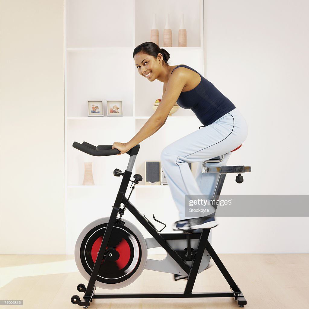 Young woman using exercise bike in home, portrait : Stock Photo