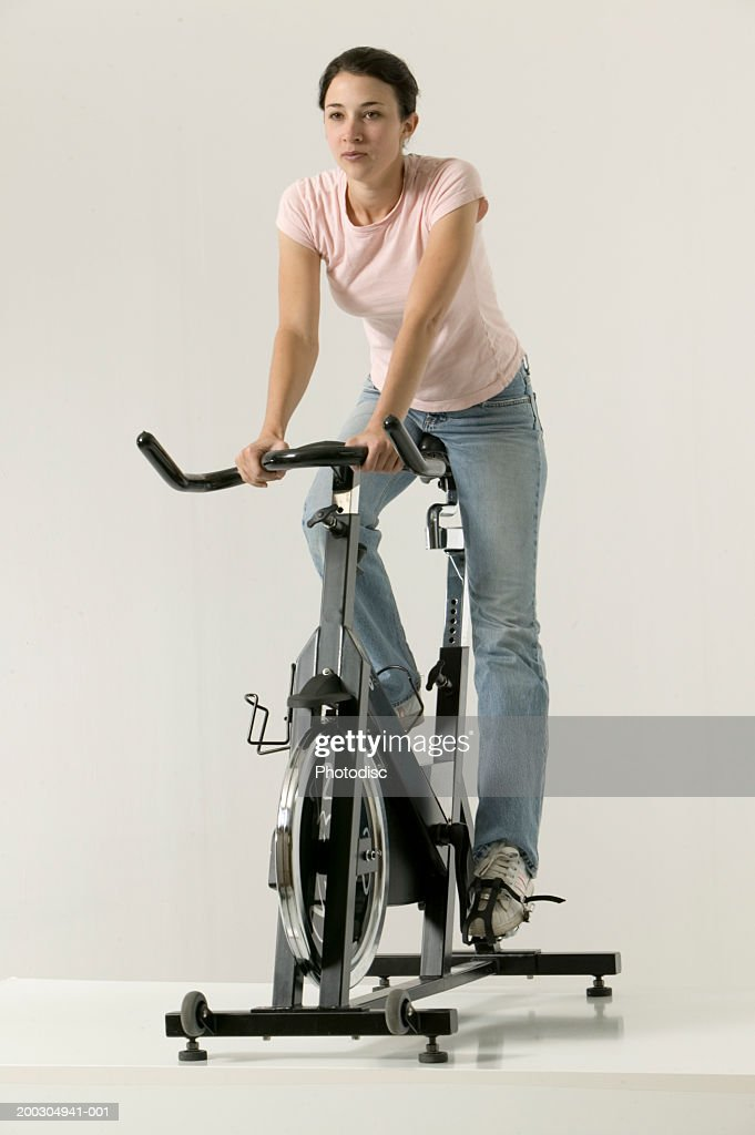 Young woman using exercise bike, posing in studio, portrait : Stock Photo