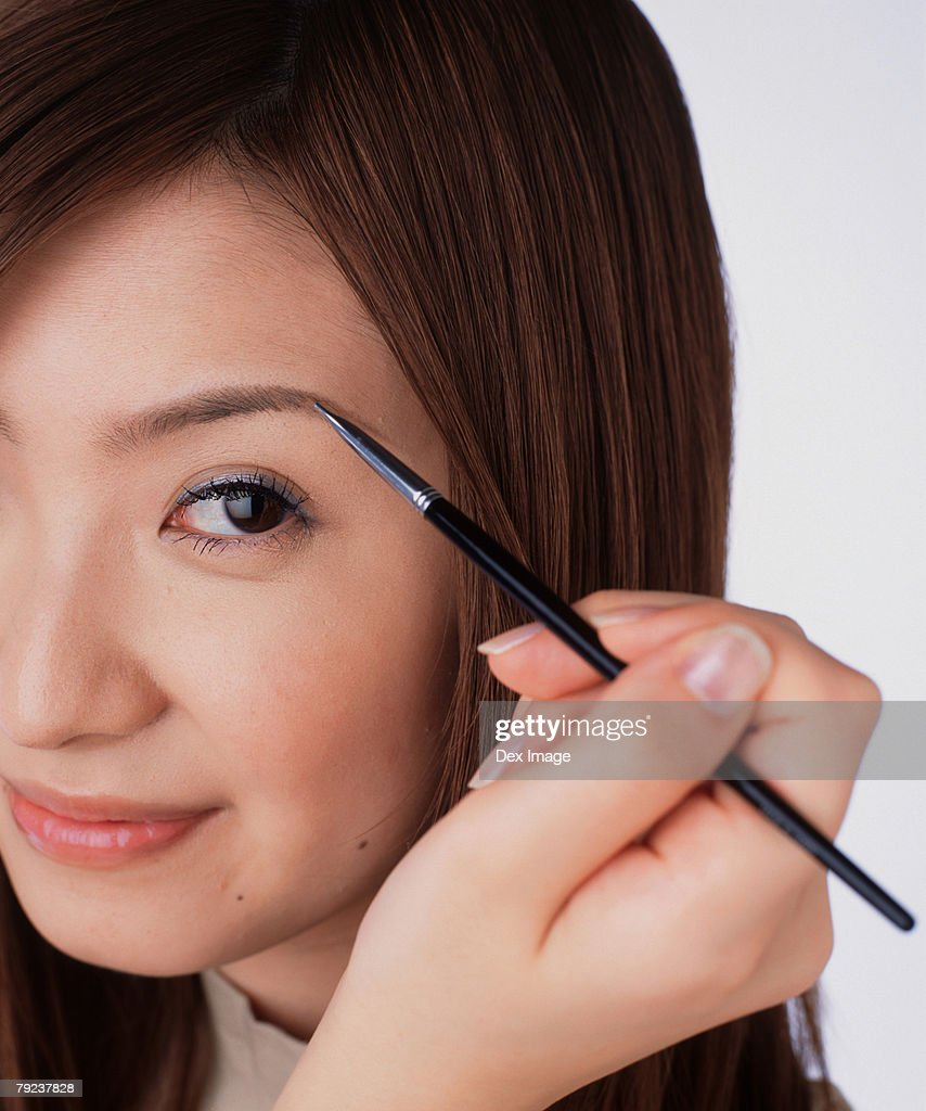 Young woman using eyebrow brush : Stock Photo
