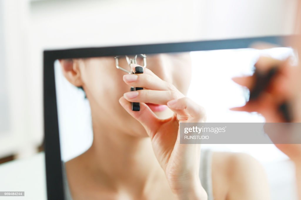 Young woman using eyelash curler : Stock-Foto