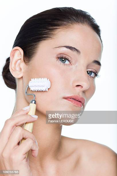 Young woman using facial massage roller
