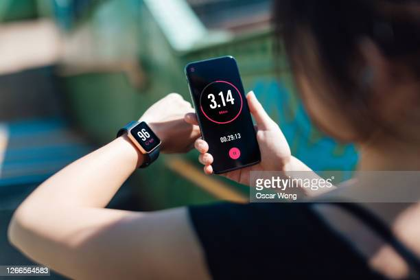 young woman using fitness app on smart phone and smart watch for tracking workout - mobile app stock pictures, royalty-free photos & images
