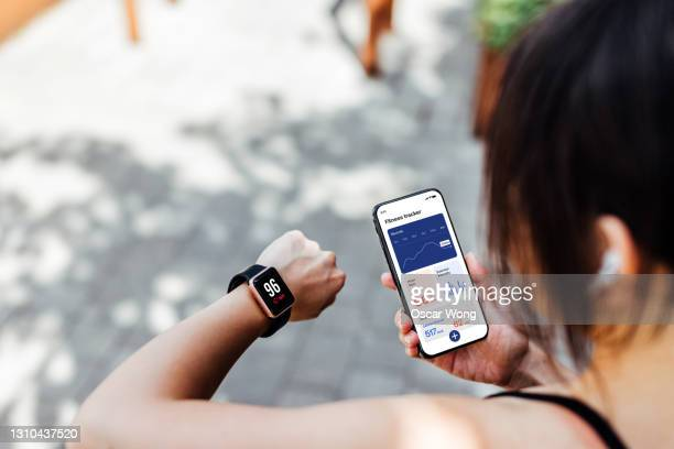 young woman using fitness tracker app on smart watch and smartphone - exercising stock pictures, royalty-free photos & images