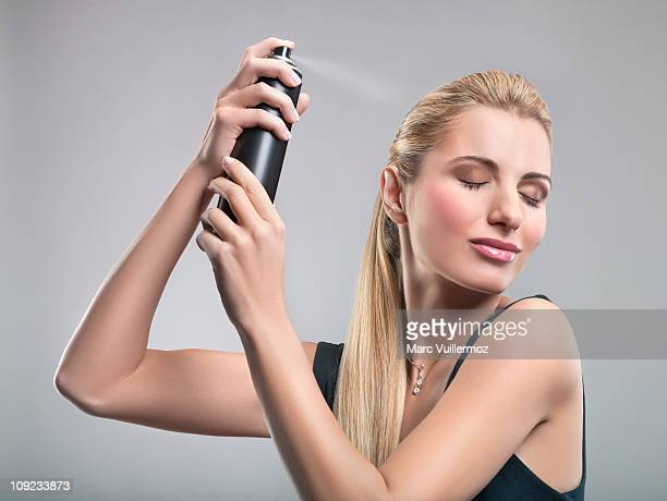 Young woman using hairspray