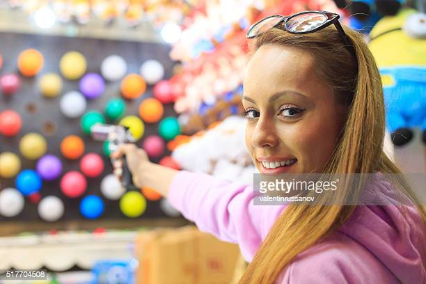Young woman using handgun for pop ballon game