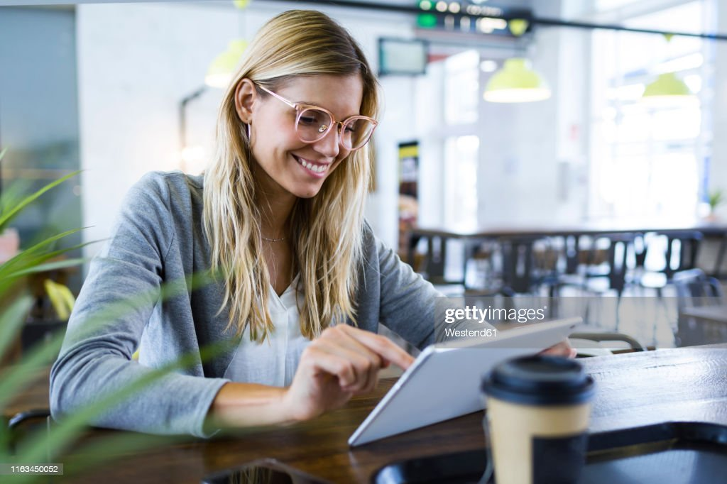 Young woman using her digital tablet while drinking coffee in the coffee shop : Foto de stock