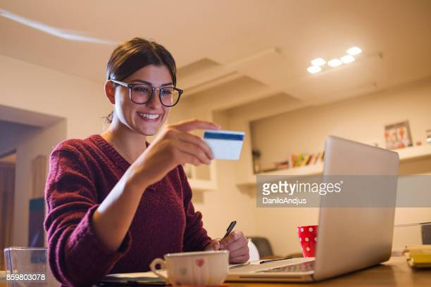 young woman using her laptop and shopping - gift card imagens e fotografias de stock