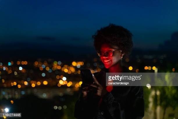 young woman using her mobile phone at night with the city at background - photo messaging stock pictures, royalty-free photos & images