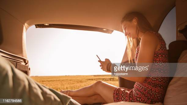 Young woman using her mobile phone while camping in her vehicle