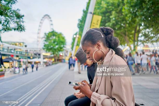 a young woman using her phone at dusk in the city - ロンドン サウスバンク ストックフォトと画像