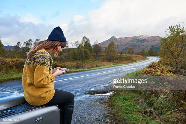 Young woman using her phone in nature
