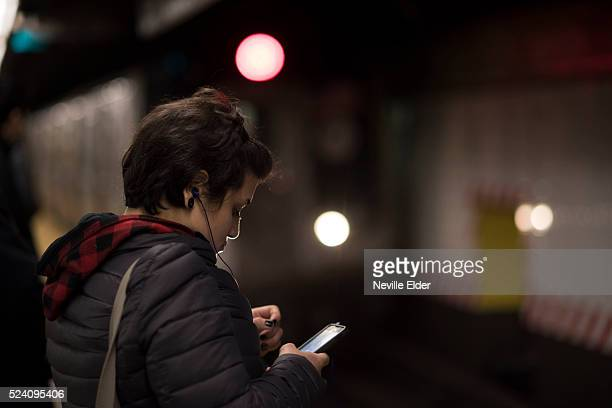 A young woman using her phone in New York City Manhattan Bridge